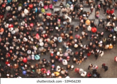 Blurred crowd of people in multicolored clothes in the city. Top view