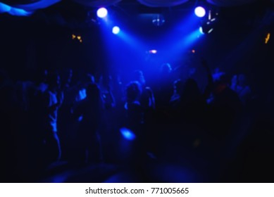blurred crowd of people on dance floor in night club under the blue lights for party and concert