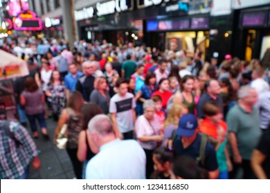 Blurred Crowd of People On Street, unrecognizable crowded population as blur urban background. Defocused blur of Times Square in New York City, midtown Manhattan at night with lights and people.
