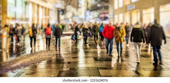 blurred crowd of people walking on night Vienna streets,