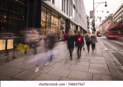Blurred crowd of shoppers walking past London fashion shops