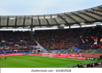 Blurred crowd of spectators on a stadium with a football match.
