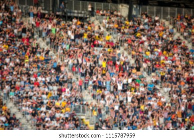 Blurred crowd of spectators in a stadium tribune at a football match