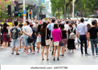 Blurred Crowd of unidentified people cross Orchard Road in Singapore.