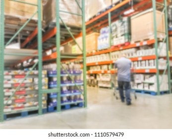 Blurred customer shopping at big boxes wholesale store in America. Large warehouse with aisles, bins and shelves of products from floor to ceiling