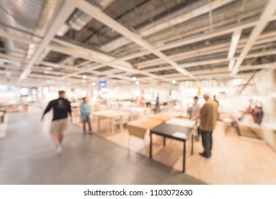 Blurred customer shopping for dining table chair set in large furniture warehouse. Defocused motion home accessories store in America.