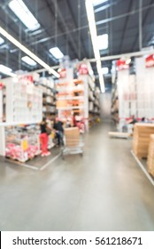 Blurred customers shopping in large furniture warehouse with forklift, cart. Row of aisles, bins from floor to ceiling. Defocused industrial storehouse interior. Inventory, wholesale, logistic, export