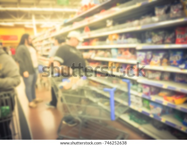 Blurred customers stock up candy, chewy and gummy goodness for holiday season. Crowed of people buying multipack, variety pack, chocolate, hard candies, bar, sour at grocery store in USA. Vintage tone