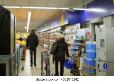 Blurred customers at the supermarket entrance