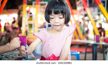 Blurred Cute girl child painting watercolor on doll. She holding paintbrush and try to beautiful it. she is creative and funny girl children.