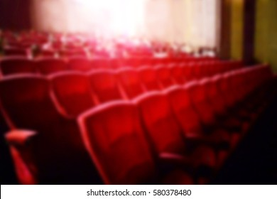 Blurred dark interior scene background of cinema and music with audience comfortable red seats and projector screen. The atmosphere in the theater before the movies start.