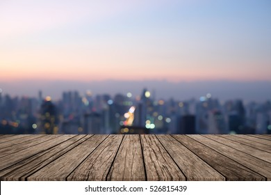 Blurred dark night city background with wood panels perspective for show promote product concept.