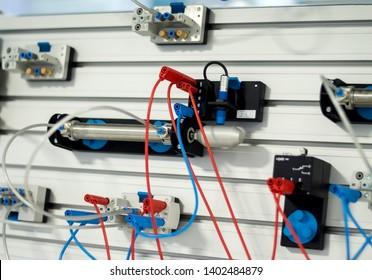 Blurred and de-focus on industrial pneumatic training kit components: pneumatic piston, solenoid valve, capacitive sensor, proximity sensor and mechanical limit sensor. PLC control.