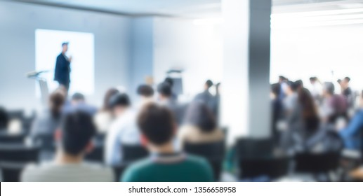 Blurred De-focused Audience in Conference Lecture Presentation Room. Corporate Presentations in Conference Hall. Seminar Speaker Giving Training to New Employees. Blurred  Hip Presenter wearing Hat.