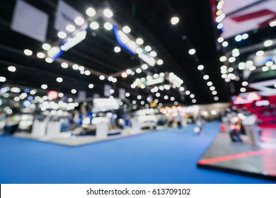 Blurred, defocused background of public event exhibition hall showing cars and automobiles, business commercial event concept.