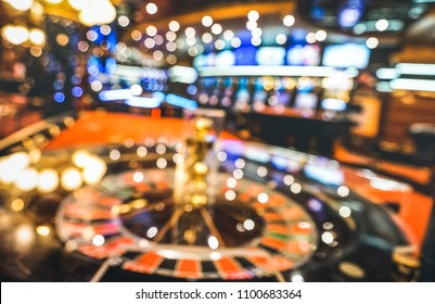 Blurred defocused background of roulette at casino saloon - Gambling concept with unfocused game room with video poker slot machines and multicolored blurry lights