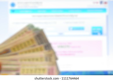 Blurred defocused Hand holding many Thailand Government lottery on Thailand Government website background for check the prize draw of the Thai Government Lottery.