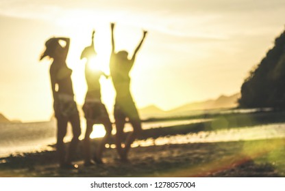 Blurred defocused silhouette of women travelers at sunset - Travel wanderlust concept with young girlfriends partying and dancing at the beach by El Nido Palawan - Warm contrasted sunshine filter
