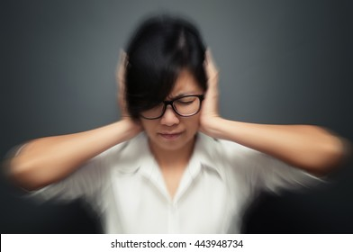 Blurred and de-focused of stress concept. Worried stressed face of asian woman expression. Glasses girl having headache with migraine. Business woman holding head with hands. Isolated background.