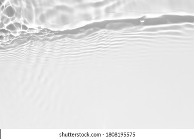 Blurred desaturated transparent clear calm water surface texture with splashes and bubbles. Trendy abstract nature background. White-grey water waves in sunlight. Copy space.