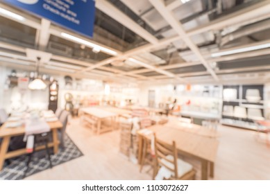 Blurred dining table chair set on display in large furniture warehouse showroom. Defocused motion home accessories store in America.