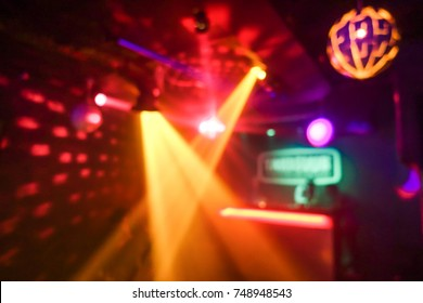 Blurred disco club with original laser color lights and disco ball - Defocused image - Concept of nightlife with cocktails, music, entertainment - Warm filter with blurry bokeh