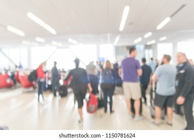Blurred diverse group of passengers with luggage waiting in line at airport boarding gate in USA. Blurry group of travelers queuing to onboard to jet bridge airplane, final boarding gate
