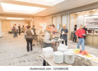 Blurred diverse group of people at continental breakfast of workshop event in suburban Dallas, Texas, USA. Defocused catering food self-service meal table at hotel hall banquet