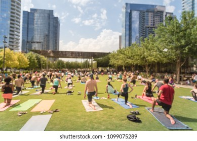 Blurred diverse group of people participating free public Yoga class at urban park. Outdoor Yoga training class on grass at summer day in Dallas, Texas, USA. Active people rolling out on colorful mats