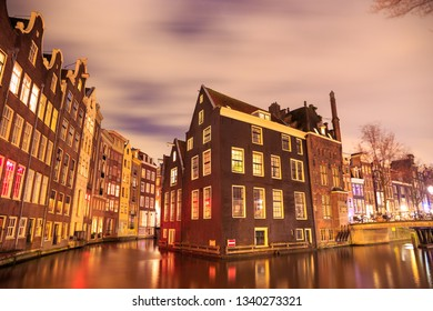Blurred dramatic night sky over traditional historical buildings on a canal, by the Armbrug bridge, in Amsterdam, Netherlands.