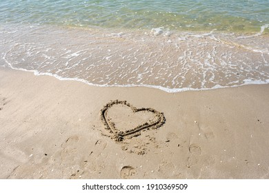 blurred of drawing heart on a yellow sand at a beautiful seascape background. Horizontal composition.