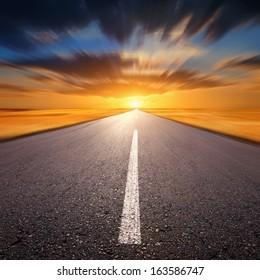 Blurred empty asphalt road at sunset