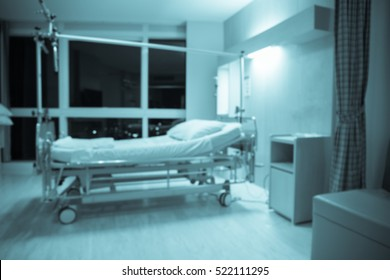 Blurred Empty patient bed On Hospital Ward in blue color tone.