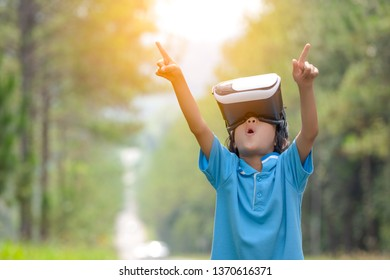 Blurred exciting kids watching virtual reality box or VR box on hills nature background