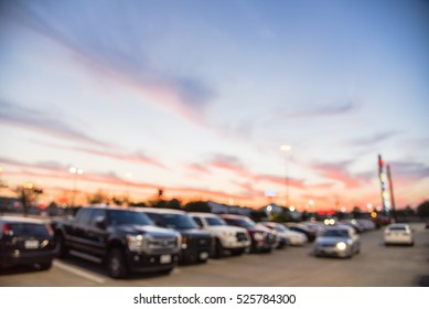 Blurred exterior view of modern shopping center in Humble, Texas, US at sunset. Mall complex with row of cars in outdoor uncovered parking lots, bokeh of retail store and light poles in background.