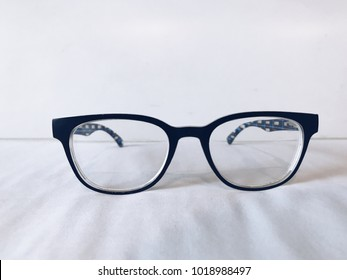 Blurred eyeglasses on white bed