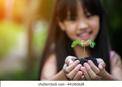 Blurred face of Asian child holding a little green plant