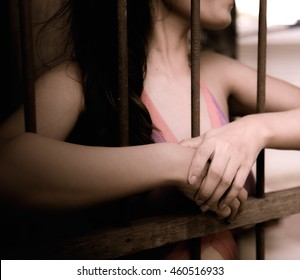 Blurred face prostitution woman grasps the bar in cage or prison with no freedom concept trying to escape or break out.