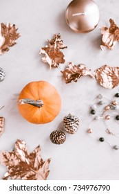 Blurred fall season flatlay on white marble background. Little pumkin, rose gold painted leaves.
