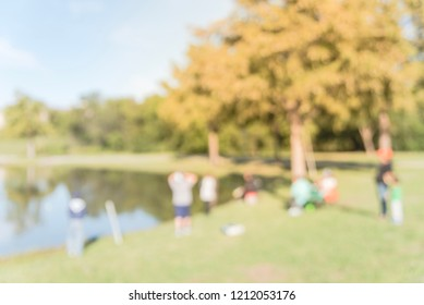 Blurred family with kids fishing in lake with green tree lush. Free community event sponsored by neighborhood association. Defocused people fishing at the lakeside of urban park