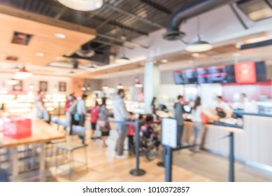 Blurred family members with stroller queuing behind stanchion barriers check-out counter at bakery in Texas, USA. Large wall mount led menu board digital signage. Abstract background crowd waiting