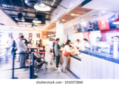 Blurred family members with stroller queuing behind stanchion barriers check-out counter at bakery in Texas, USA. Big wall mount led menu board digital signage. Abstract crowd waiting. Vintage tone