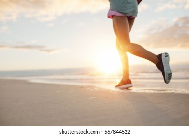 Blurred Feet of young woman jogging on the beach. Fitness female on morning run at sea shore.