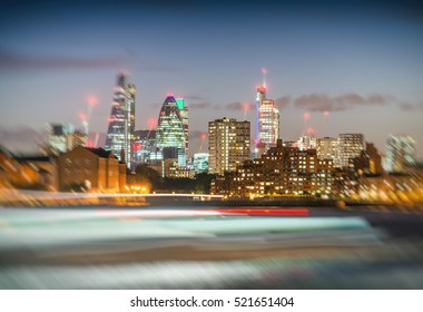 Blurred ferry light trails with London City skyline, night view.