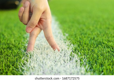 Blurred fighting hand sign on a fresh green football field.
