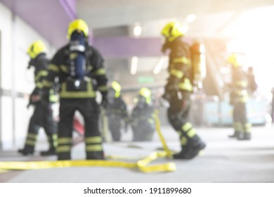blurred firefighters training spraying water to fire