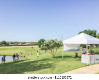 Blurred fishing community event with tent setup at neighborhood in Irving, Texas, USA. Family with kids fishing, summer leisure activities, outdoor recreation concept