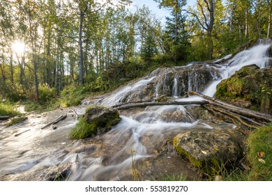 Blurred flowing stream cascading down a waterfall with the sun bursting through the trees at Big Hill Springs Provincial Park, Alberta, Canada