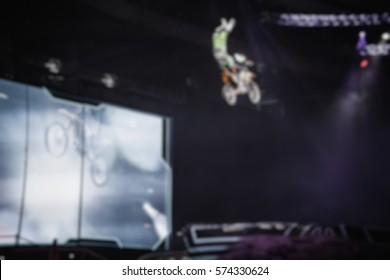 Blurred fmx extreme sport competition show background.Freestyle motocross athlete jump high from big air ramp performing dangerous cliff hanger trick on FMX motor bike.Out of focus back ground blur