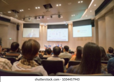 Blurred focus Audience listening speaker making speech with big LED presentation screen on stage in conference hall, seminar, meeting room, view from listener people Education and business background